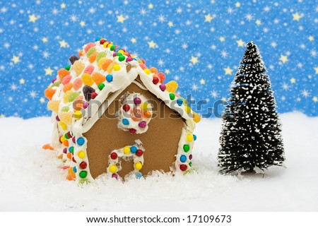 Gingerbread house and tree on snow with star background, gingerbread house - stock photo