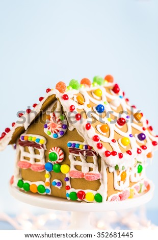 Gingerbread house decorated with white royal icing and bright candies.