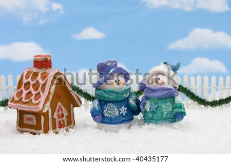 Gingerbread house on snow with a snowman and sky background, gingerbread house - stock photo