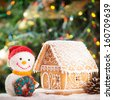 gingerbread house over on the snow and lovely handmade snowman - stock photo