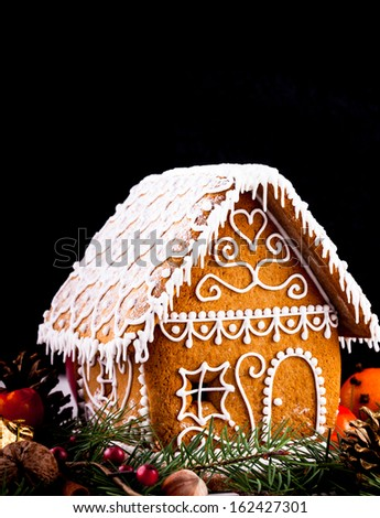 gingerbread house with christmas decorations on a black backgrond - stock photo