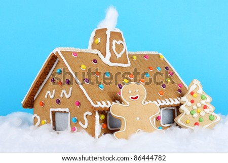 Gingerbread house with gingerbread man and christmas tree. - stock photo