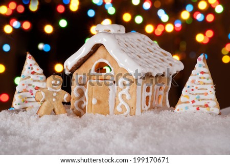 Gingerbread house with gingerbread man and christmas trees. Gingerbread man cookie standing in snow beside house. Christmas decoration. - stock photo