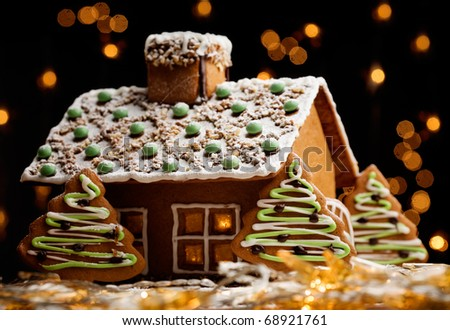 Gingerbread house with lights inside, dark background - stock photo