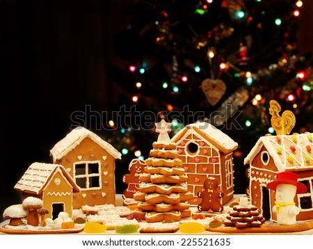 Gingerbread houses, gingerbread Christmas Tree, homemade cookies, on the background of the Christmas tree - stock photo