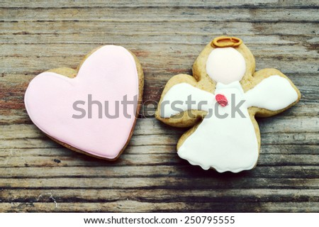 Gingerbread in a shape of heart and angel with pink and white icing on wooden table - stock photo