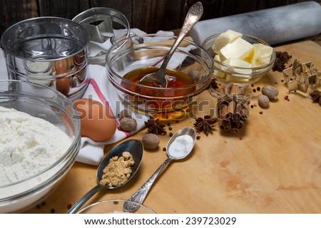 Gingerbread ingredients: butter, flour, honey, sugar, egg, ginger, baking soda, cinnamon, star anise, nutmeg, pepper - stock photo
