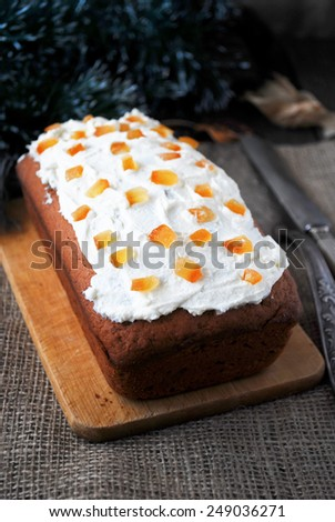 Gingerbread loaf cake decorated with white cream cheese frosting and candied orange peel on wooden cutting board - stock photo