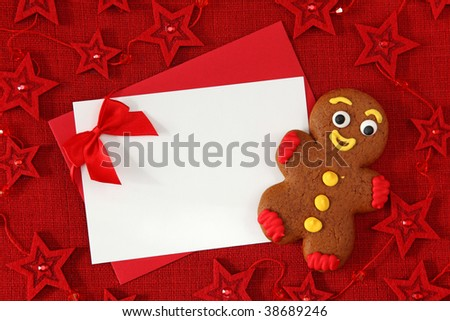 Gingerbread man and blank card on red background - stock photo