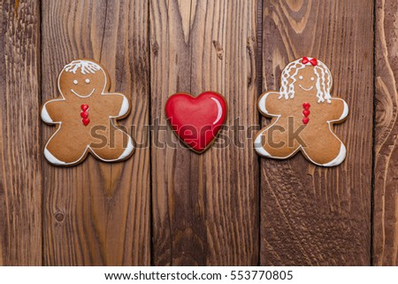 Gingerbread man and women with a heart on the wooden background. Valentine's day card.