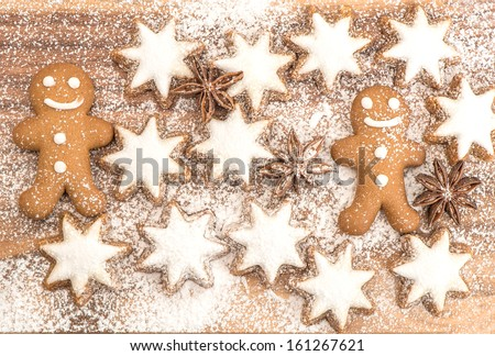 gingerbread man cookie, cinnamon stars and star anise on wooden background. christmas bakery - stock photo