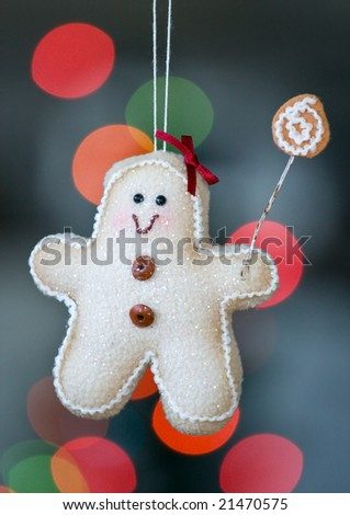 Gingerbread man decoration hangs from a christmas tree - stock photo