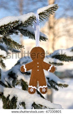 gingerbread man hanging on a firtree branch - stock photo