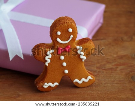 Gingerbread man in front of wrapped gift