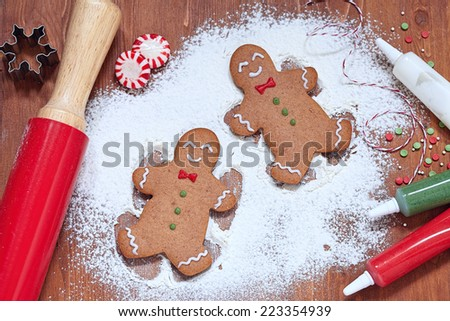 gingerbread man making a snow angel in white flour - stock photo