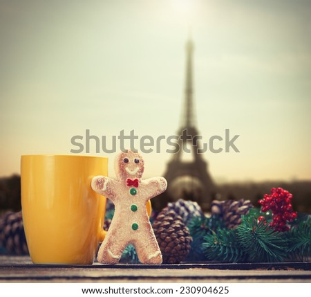 Gingerbread man near cup and Pine branch with Eiffel tower on background - stock photo