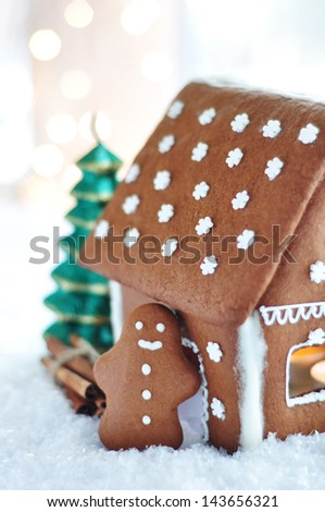 Gingerbread man standing by the Gingerbread house - stock photo