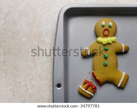 Gingerbread man with broken leg on baking sheet, close-up - stock photo