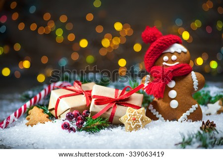 Gingerbread man with Christmas presents in snow - stock photo