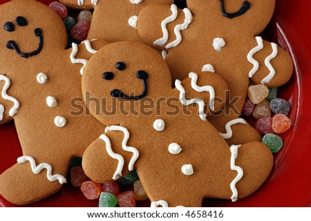 Gingerbread men arranged on red ceramic plate with gumdrops - stock photo