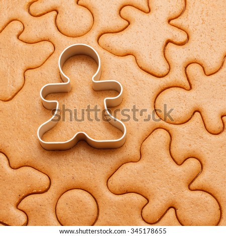 Gingerbread men background with cutter. Christmas baking texture