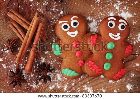Gingerbread men on wooden background - stock photo