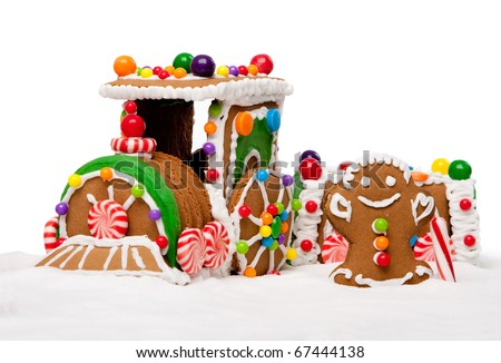 Gingerbread Polar Express Train and happy man for Christmas covered with snow and colorful candy on a winter landscape, isolated. - stock photo