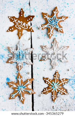 Gingerbread snowflakes decorated with icing and sprinkling sugar on a white background - stock photo