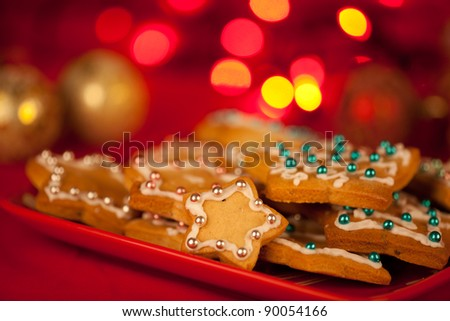 gingerbread stars decorated and served on the red plate. - stock photo