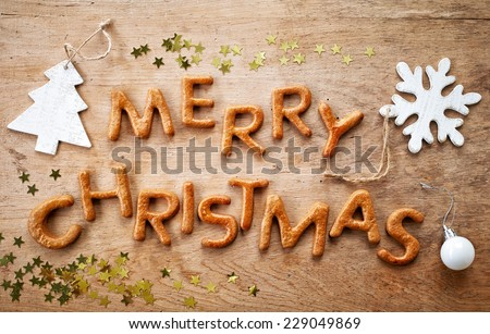 Gingerbread words Merry Christmas on old wooden table - stock photo