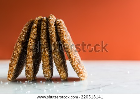 Gingersnap cookies coated with sugar crystals. Close up of cookies standing sideways on edge on a white marble countertop. Texture detail. Copy space. - stock photo