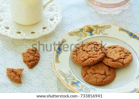 Gingersnaps and tea on old fashioned dishes in horizontal format and shot in natural light