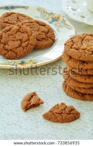 Gingersnaps and tea on old fashioned dishes in vertical format and shot in natural light