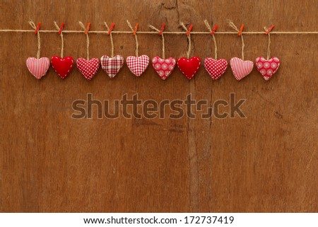 Gingham Love Valentine's hearts natural cord and red clips hanging on rustic plywood texture background, copy space - stock photo