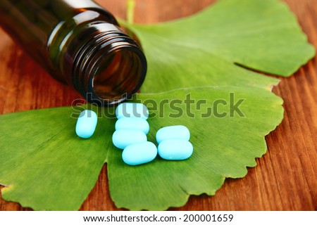 Ginkgo biloba leaves and medicine bottle on wooden background - stock photo