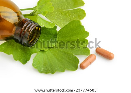 Ginkgo biloba leaves and medicine bottles with pills isolated - stock photo