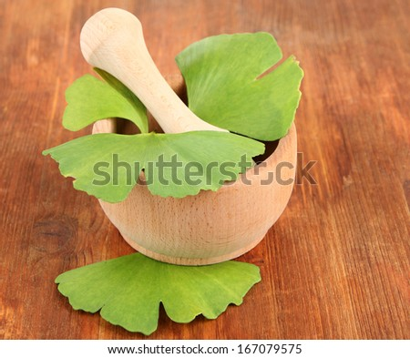Ginkgo biloba leaves in mortar and pills on wooden background - stock photo