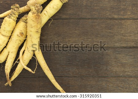 Ginseng root is placed on the wooden floor; Herbal Health Care. - stock photo