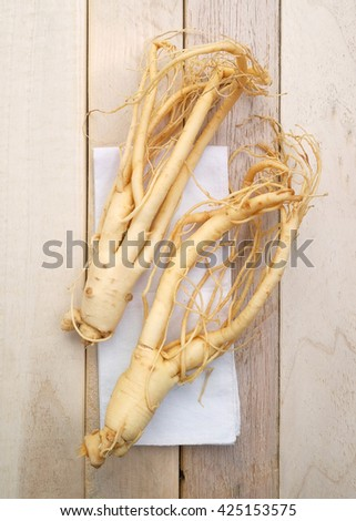 Ginseng root,Korean ginseng on wood background - vintage filter. - stock photo