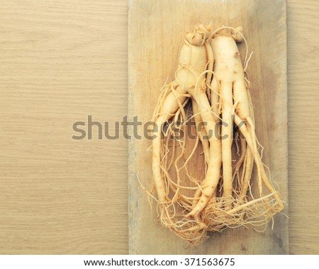 Ginseng root with space on wooden cutting boards - vintage filter. - stock photo