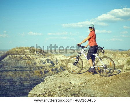 Girl a bike in mountains. An active holiday. Fitness, sports. Lifestyle.      - stock photo