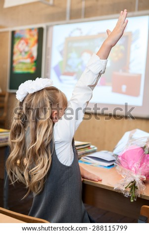 Girl a student raising hand up for answer at school lesson, rear view