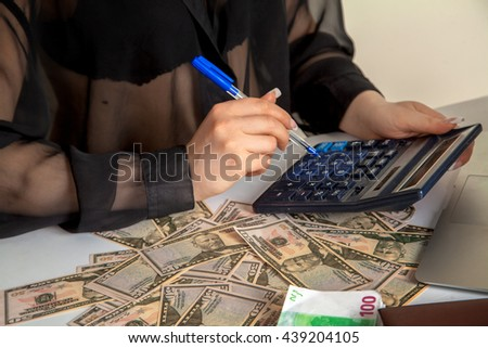 girl accountment counts on a calculator a lot of money, horizontal photo of money and bank employee - stock photo