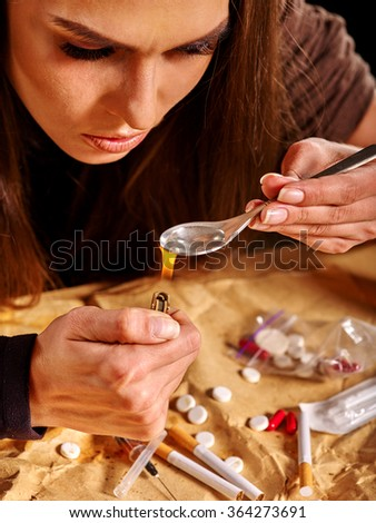 Girl addict with heroin spoon and lighter. Sossial issues on black background. - stock photo