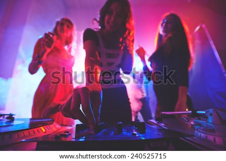 Girl adjusting deejay equipment with dancing friends behind - stock photo