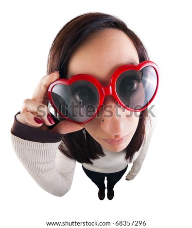 Girl adjusting her heart-shaped sunglasses and looking straight at camera. Shot using a fish eye lens from high angle. - stock photo