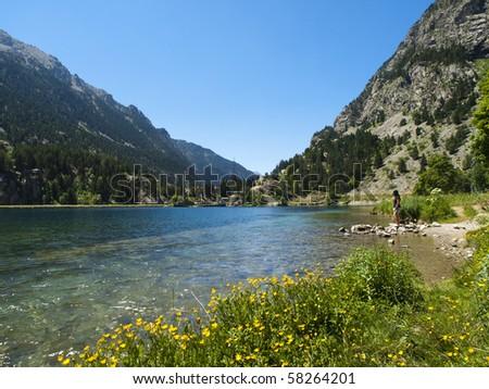 Girl admiring a beautiful mountain lake in the Pyrenees - stock photo