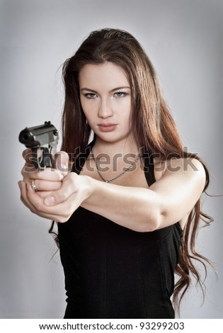 Girl aiming a gun, focus on the person - stock photo