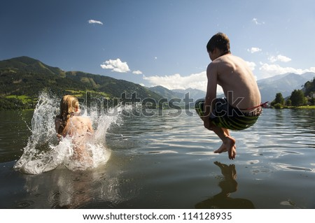 girl already in the splashing water and boy in the air while they where jumoing into a lake, with nice nature and mountains in the back - stock photo