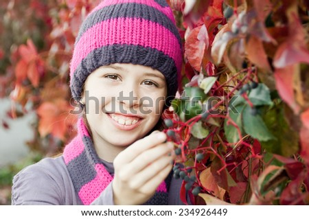 Girl among red autumn leaves - stock photo